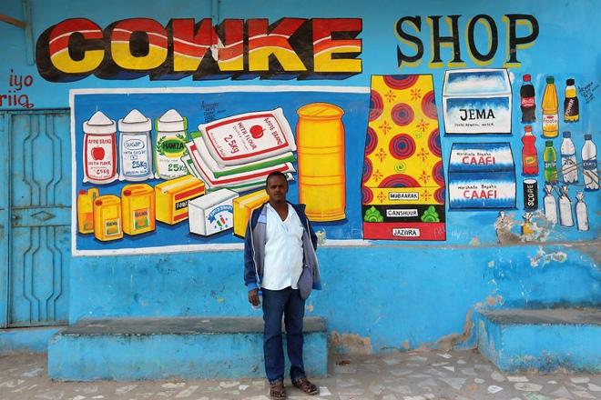 Muawiye Hussein Sidow và một tác phẩm vẽ lên tường của anh. Ảnh: Reuters.